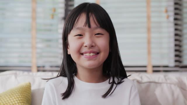 stockvideo's en b-roll-footage met portret weinig glimlach en het kijken naar camera bij woonkamer. aziatisch meisje dat videovraag aan haar ouder thuis opneemt. - kindertijd
