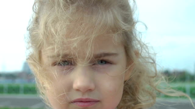 Portrait little young blonde girl with blue eyes. Wind blowing hair. Slow Motion. Cute child confident pretty. Windy weather.