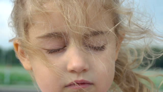 Portrait little young blonde girl with closed eyes. Wind blowing hair. Slow Motion. Cute child confident pretty. Windy weather. Portrait little young blonde girl with closed eyes. Wind blowing hair. Slow Motion. Cute child confident pretty. Windy weather. eyes closed videos stock videos & royalty-free footage