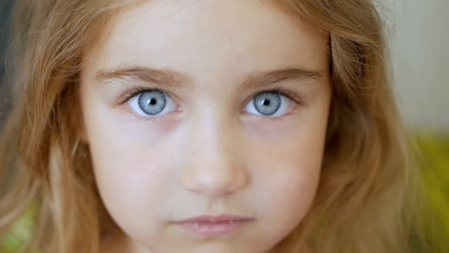 portrait little young girl with blue eyes looking at camera - bambine femmine video stock e b–roll