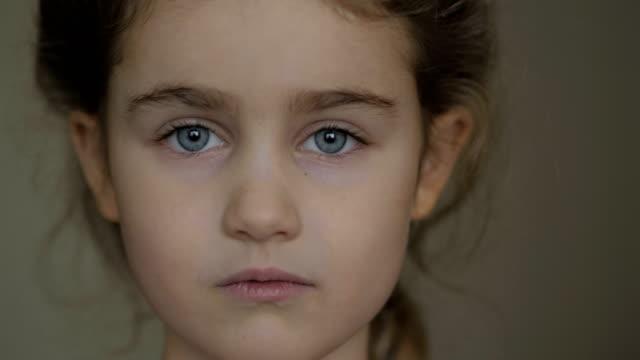 portret mała młoda dziewczyna z niebieskimi oczami patrząc na aparat. małe poważne dziecko patrzące na kamerę. zbliżenie. pomieszczeniach.  smutna dziewczynka portret szuka. - surowy obraz filmowy filmów i materiałów b-roll