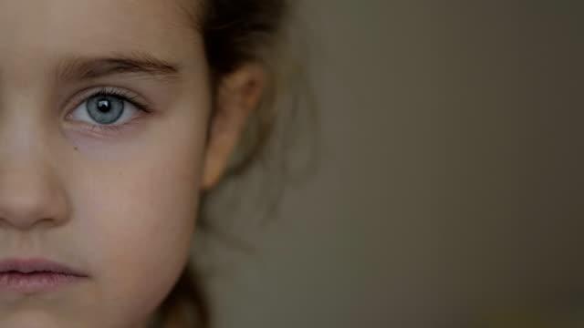 stockvideo's en b-roll-footage met portret kleine jonge meisje met blauwe ogen kijken naar camera. jong ernstig kind kijkt naar de camera. close-up. binnen.  verdrietig klein kind meisje portret op zoek. - kindertijd