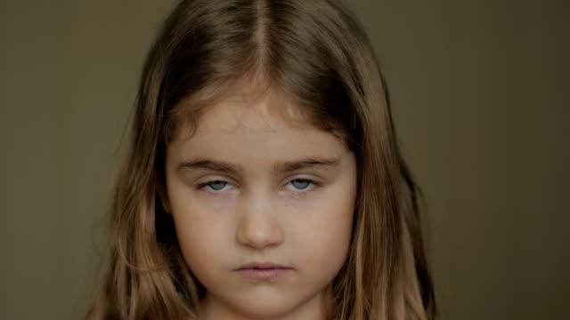 porträtt liten ung flicka med blå ögon tittar på kameran. unga allvarliga barn tittar på kameran. närbild. inomhus.  ledsen liten unge flicka porträtt ser. - flickor bildbanksvideor och videomaterial från bakom kulisserna