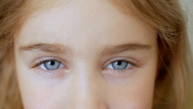 Portrait little young girl with blue eyes looking at camera. Young serious kid looking at camera. Closeup Portrait little young girl with blue eyes looking at camera. Young serious kid looking at camera. Closeup close to stock videos & royalty-free footage