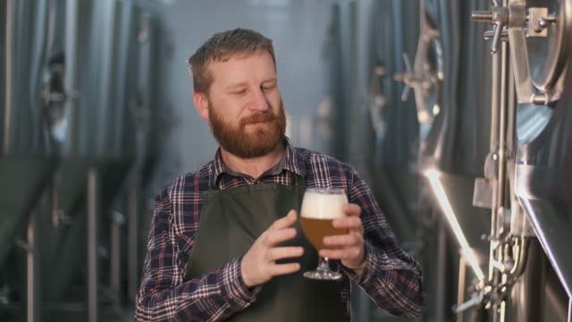 Portrait. male brewer checks the color of freshly brewed beer from a beer tank while standing in a brewery
