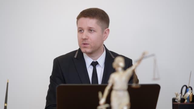vídeos de stock, filmes e b-roll de advogado do homem do retrato que fala na estátua do themis no escritório de lei. consulta jurídica - assistente jurídico