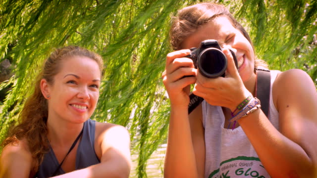 Portrait of 2 young women smiling and taking a photo towards the camera