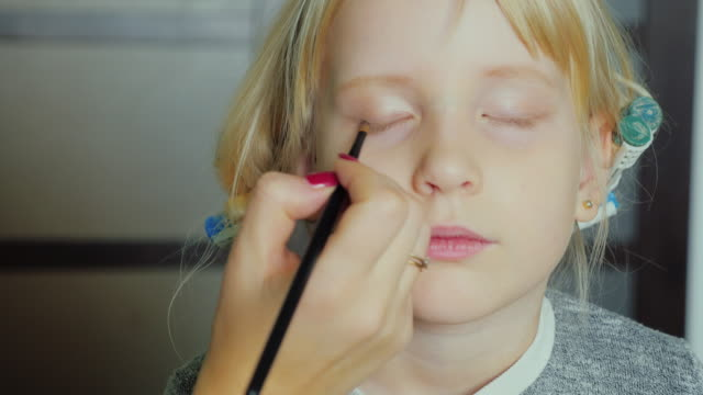 Portrait of 5 years old girl doing makeup. curlers on her head video