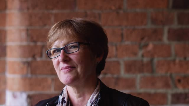 Portrait of 50-Something Woman Against Brick Wall video