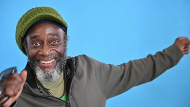 57 yaşındaki siyah adamın gülümseyip dans eden portresi - renkli arka fon stok videoları ve detay görüntü çekimi