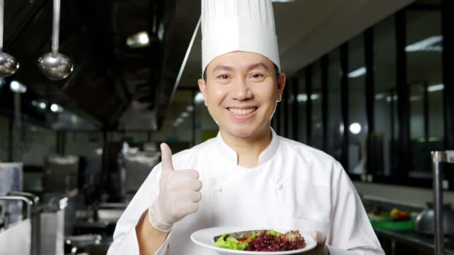 Portrait of a Asian male chef working in a restaurant kitchen, presenting plate of food to camera,Close up
