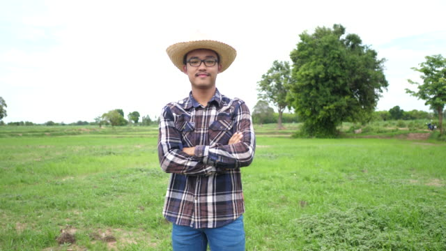 Portrait of a Asian young male farmer in an organic agricultural field - video
