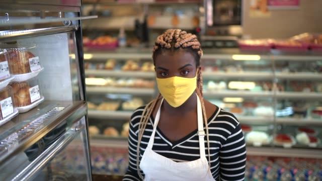 vídeos de stock e filmes b-roll de portrait of a bakery employee using face mask - afro latino mask