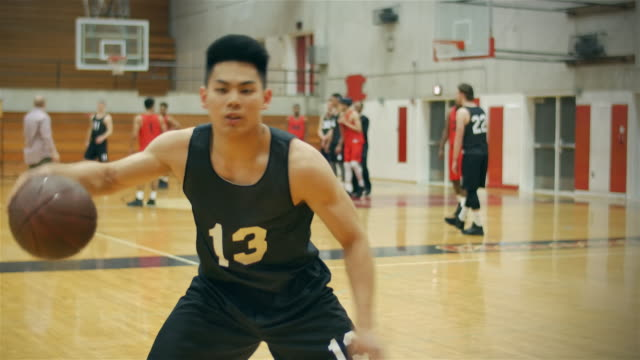 Portrait of a basketball player dribbling the ball intensely, in front of a court video
