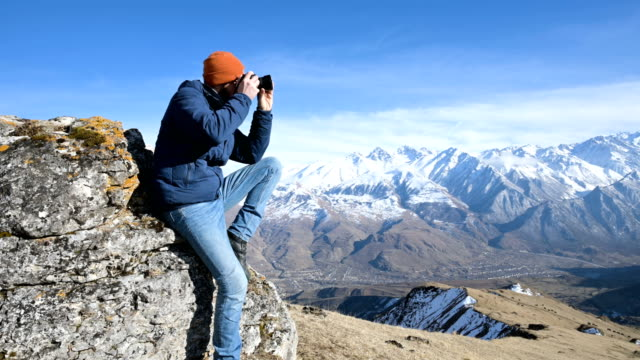 Portrait of a bearded traveler photographer in sunglasses and a cap sits on a rock with mirror camera in his hands and take a picture against the backdrop of mountains Portrait of a bearded traveler photographer in sunglasses and a cap sits on a rock with mirror camera in his hands and take a picture against the backdrop of mountains 4k action movie stock videos & royalty-free footage