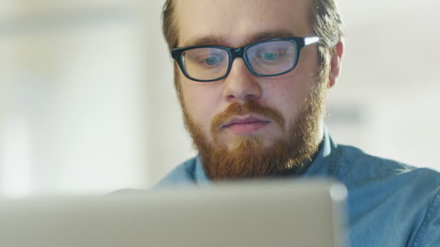 Portrait of a Bearded Young Man Wearing Glasses Sitting in His Office Working on a Computer. Computer Screen Reflects in His Glasses. video
