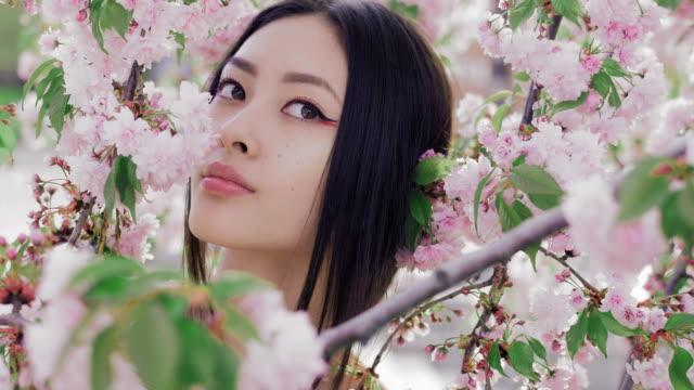春の花のツリーに対して屋外美しいアジアの少女の肖像画 ビデオ