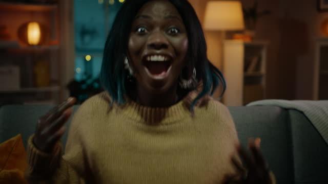 porträt von einem schönen schwarzen mädchen sitzen auf einer couch zu hause in der nacht, film im fernsehen. sie bekommt wirklich aufgeregt und emotional. - aufregung stock-videos und b-roll-filmmaterial