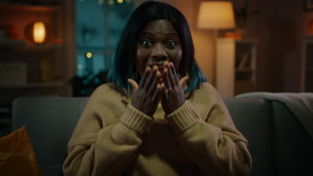 portrait of a beautiful black girl sitting on a couch at home at night, watching horror movie on tv. she gets really scared and emotional. - sorpresa video stock e b–roll