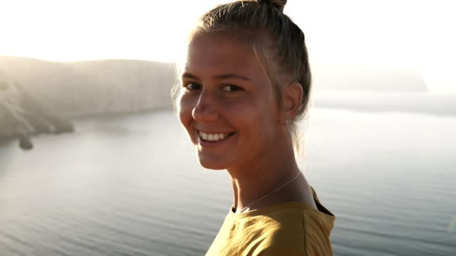 Portrait of a beautiful blonde traveler girl in yellow T shirt on the edge of the cliff, admiring the view and smiling to the camera. Sea view, mountains and sky on the background video
