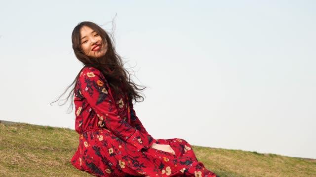 カメラに微笑む草原に座っている赤いドレスを着た美しい中国の若い女性の肖像画は、彼女の黒い長い髪、4k映像、スローモーションを吹く風をお楽しみください。 - スーパーモデル点の映像素材/bロール