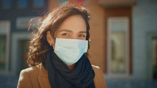 Portrait of a Beautiful Dark Haired Young Woman Wearing Protective Medical Face Mask and Standing on the Street. Safe and Happy Woman Practicing Social Distancing, Quarantine. Blurred City Background