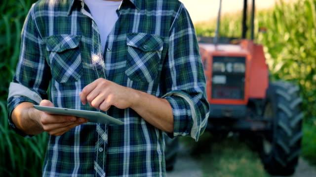 vidéos et rushes de portrait d'un jeune agriculteur bel (étudiant) travaillant dans le domaine avec un tracteur, réussi souriant, heureux, en chemise, champ de maïs. - équipement agricole
