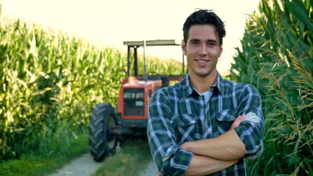 stockvideo's en b-roll-footage met portret van een mooie jonge boer (student) werken in het veld met een trekker, succesvolle lachend, blij, in een shirt, maïsveld. - portrait background