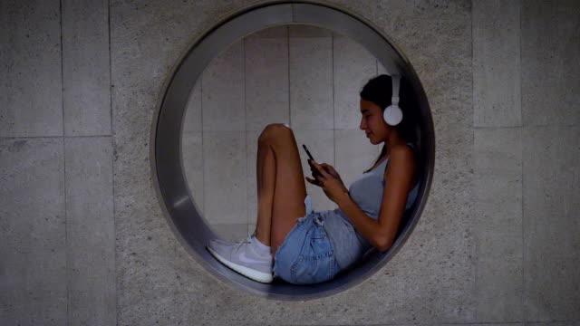Retrato de uma linda jovem (mulher) ouvir música no telefone, dançando, sorrindo feliz, no metrô. Turismo de conceito, amor para viagens, comunicação, liberdade, vida amorosa, estilo de vida, as pessoas - vídeo