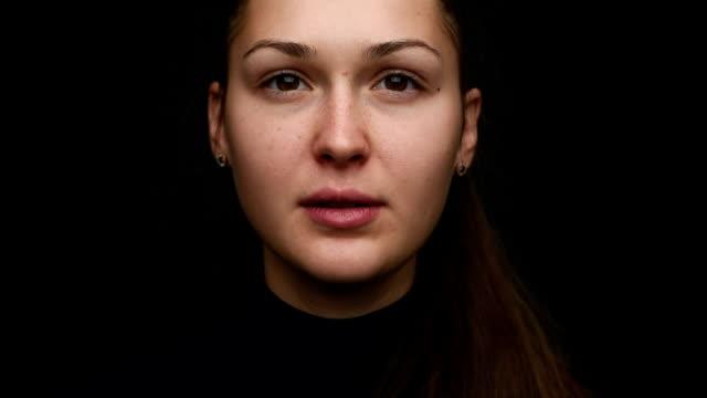 porträt von einem schöne junge mädchen auf einem schwarzen hintergrund. close-up. dolly - ernst stock-videos und b-roll-filmmaterial