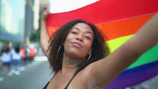 Portrait of a beautiful young woman holding rainbow flag during LGBTQI parade – film
