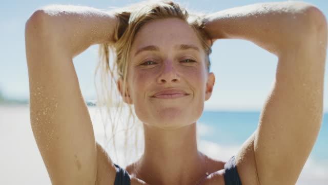 stockvideo's en b-roll-footage met portret van een mooie jonge vrouw op het strand - blond haar