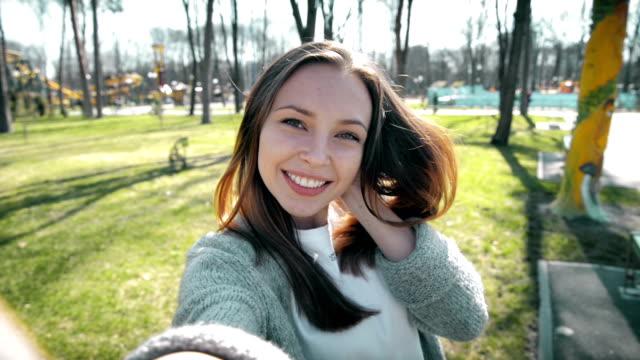ポートレートの美しい若い女性の写真を、公園内では、スマートフォンです。 - セルフィー点の映像素材/bロール