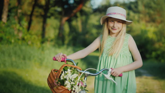 portrait of a blond girl with a bicycle. with her basket of wildflowers. looks at the camera - cestino della bicicletta video stock e b–roll