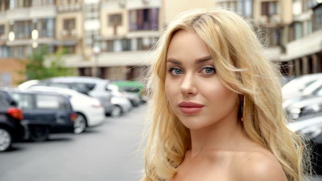 vídeos y material grabado en eventos de stock de retrato de una rubia con labios llenos y ojos azules sobre un fondo de estacionamiento - ojo morado