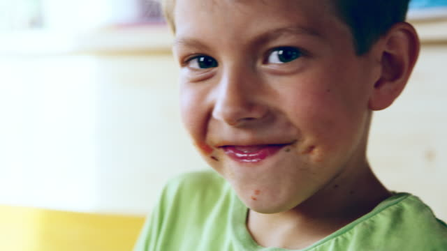 CU Portrait of a boy cleaning his mouth after eating Close up shot a young boy cleaning his dirty mouth while he is smiling and looking at the camera. Slovenia boys stock videos & royalty-free footage