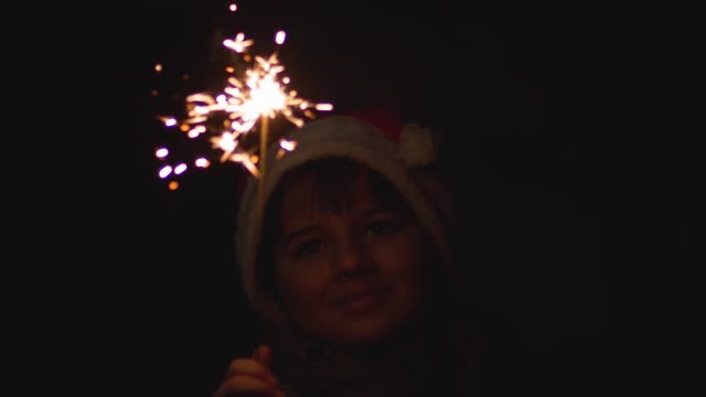 portrait of a boy in a Santa Claus hat with a Bengal fire video