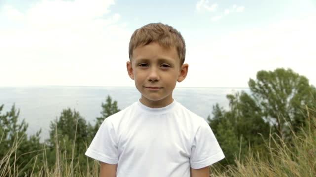 portrait of a boy in a white t-shirt - maglietta bianca video stock e b–roll