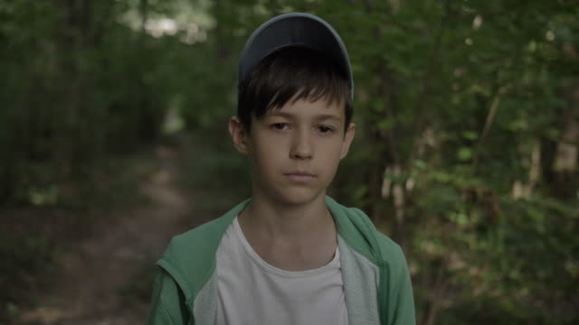 portrait of a boy in the forest looking at the camera, forest path video