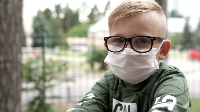 Portrait of a boy in the street in a protective mask to prevent coronavirus. The concept of COVID-19 infection and pandemic. video