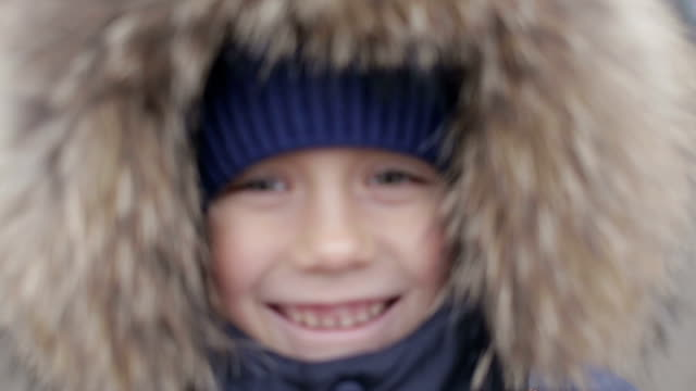 Portrait of a boy in winter jacket with hood on his head video