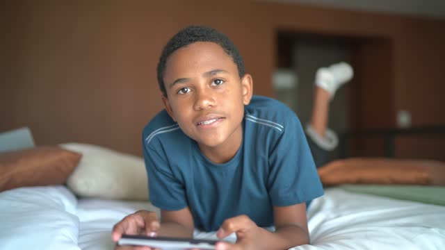 Portrait of a boy playing on smartphone lying in bed at home video