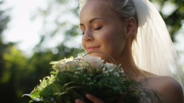 Portrait of a bride in wedding dress with flowers in a sunny park. video