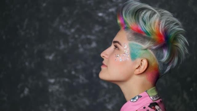 stockvideo's en b-roll-footage met portret van een heldere vrouw met geverfd haar, een kort kapsel en een kapsel tegen een grijze achtergrond. felgekleurde haarverf. - roze haar