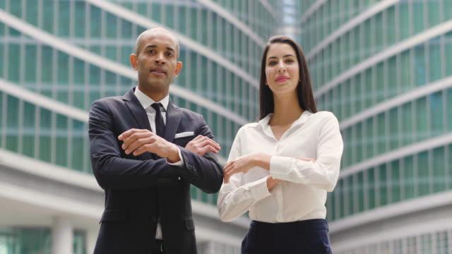 stockvideo's en b-roll-footage met portret van een zakenman en vrouw van verschillende etniciteit, kijkend naar de camera en glimlachen, het oversteken van hun armen. - portait background