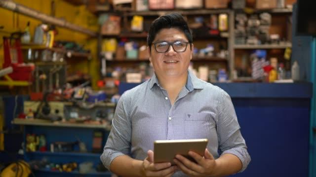 porträtt av en affärsman med hjälp av tablet i en bilverkstad - mekaniker bildbanksvideor och videomaterial från bakom kulisserna
