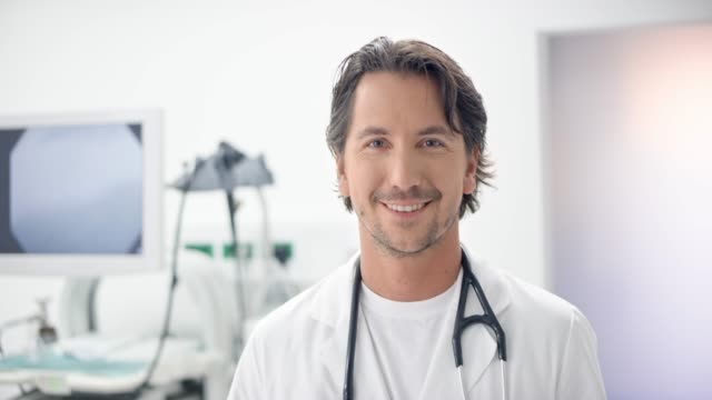 Portrait of a Caucasian male doctor using a digital tablet in his office and smiling into the camera video