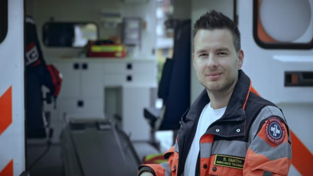portrait of a caucasian male paramedic standing by the stretcher - paramedic stock videos and b-roll footage