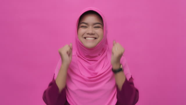 手を上げた陽気なイスラム教徒の女性のスロー MO ポートレート ビデオ