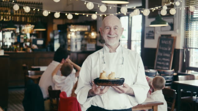 Portrait of a chef holding empanadas in Argentinian restaurant